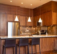 Walnut cabinets, a stunning granite countertop, and a metallic backsplash.  http://newyorkartistic.com