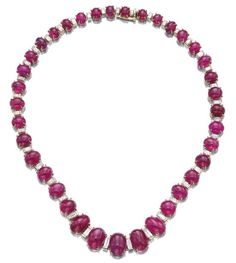 RUBY AND DIAMOND NECKLACE, BULGARI. Designed as a graduated line of cabochon rubies set between baguette diamonds, signed Bulgari.