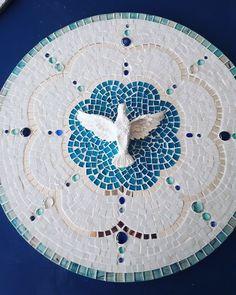 Mandala com base de MDF, revestida com pastilhas de vidro, gemas de vidro e espelhos. Decorada com divino Espírito Santo de resina.