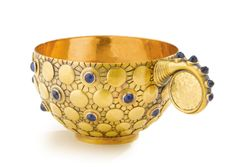 A Fabergé Gold and Gem-Set Charka, Workmaster Michael Perchin, St. Petersburg, circa 1895 - Estimate: 7,000 - 9,000 USD  LOT SOLD. 34,375 USD (Hammer Price with Buyer's Premium)  the cup engraved with a radiating pattern set with series of graduated gold bosses with saphires, with handle set with gold 1779 ruble coin and mounted in cabachon saphires...