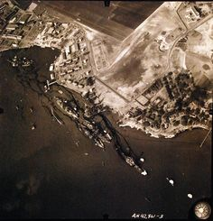 "80-G-387565: Pearl Harbor Attack, 7 December 1941. Aerial view of ""Battleship Row"" moorings on the southern side of Ford Island, 10 December 1941, showing damage from the Japanese raid three days earlier. In upper left is the sunken USS California (BB-44), with smaller vessels clustered around her. Diagonally, from left center to lower right are: USS Maryland (BB-46), lightly damaged, with the capsized USS Oklahoma (BB-37) outboard."