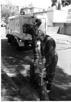 PH Stonnington Council worker vacuuming leaves from street;
