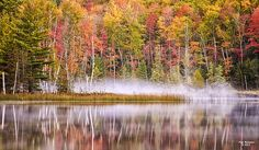 The early morning fog and fall color reflections on a lake in northern Michigan.
