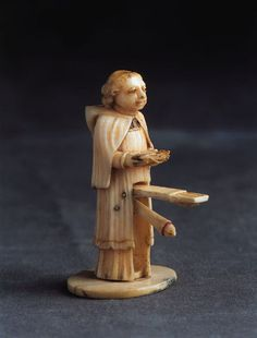 An amusing erotic ivory carving of a monk with a large phallus. His bible painted with the words 'Look Under My Book'. Late 18th - Early 19th century.