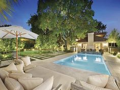 Landscaped pool design using natural stone with retaining wall & decorative lighting