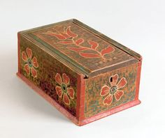 """Pook & Pook. October 24th & 25th 2008. Lot 584. Estimated: $8K - $12K. Realized Price: $6435. Pennsylvania painted pine slide lid box, early 19th c., the lid decorated with a large red tulip on a green and brown mottled ground, the sides with red, white, and green floral devices, 6 1/2"""" h., 9"""" w., 14"""" d."""