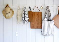 the kitchen entryway pegs hold everything from hats to cutting boards   via coco kelley