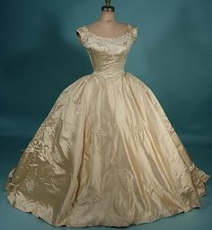 """1956 Priscilla candlelight satin gown. Wide nearly off the shoulder bodice, """"v"""" piped bodice at fitted waist, ribbons, lace & sequins on the shoulders & around the neckline.  Lace applique, pearls & sequins on the skirt."""