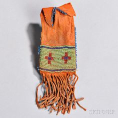 Blackfeet Beaded Hide Paint Bag, c. 1880, with red ochre overall and beaded on one side, in the form of a miniature paint bag, (minor bead loss), lg. 5 1/2 in. Estimate $800-1,200