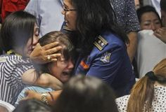 Relatives of passengers of the missing AirAsia Flight 8501 react upon seeing the news on television about the findings of bodies on the waters near the site where the jetliner disappeared, at the crisis center at Juanda International Airport in Surabaya, East Java, Indonesia, Tuesday, Dec. 30, 2014. (AP Photo/Trisnadi)