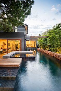 Un joli couloir de nage avec spa à mosaïque noire débordant. L'accès au bassin semi-enterré se fait depuis la terrasse en bois. Une belle #piscine de ville. @Vivre ma Piscine