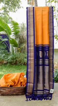 This gadwal silk is in gold yellow with gold zari bhuttas all over. the complementing border and pallu are in navy blue intricately woven with gold zari making it perfect for celebrations and parti…