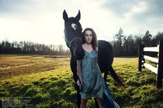 Kimberley Rae. the girl and her horse she leaded the beast. black with white spotted head turned into her. she is strong and powerful. the meadow and field. two as one