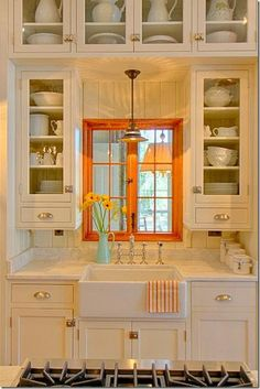 Great stage for sink with a pretty window and glass fronted upper cabinets to create symmetry with farmer's sink.