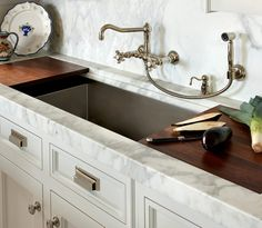 kitchen sink with shelf for cutting board or drain tray . lovely wall mounted faucet . O'Brien Harris Interior Design