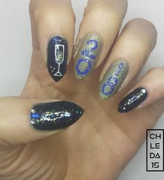 """Thumb & pinky with dark blue sparkle for base with special sparkle topcoat & rhinestones near cuticles. Index with dark blue sparkle base with hand painted flute glass filled with gold holo and surrounded with bubble dots. Middle & ring with gold holo base & dotticure numbers in blue & blue sparkle to read """"2018"""" Nail Polish: Color Club 1001 """"Williamsburg"""", Girly Bits Cosmetics """"Anniversary Crashers"""", Finger Paints 806109 """"Daubigny's Garden"""" & China Glaze 1410/82706 """"Let's Dew It"""" - Jan 2018"""