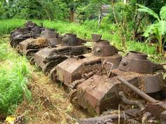 A large number of rusting Japanese tank hulls lined up on a island for tourists to explore by islanders.