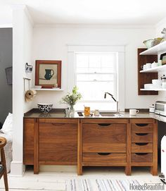 A Scandinavian-Inspired Kitchen in New York ~ this airy kitchen is accented with deep wood and stone details, featuring dark Bornholm wooden cabinetry, a shelf for interchanging framed artwork, dark Silestone countertops and light backsplash, silver appliances and a chalkboard facade pull-out pantry next to refrigerator | House Beautiful | interior designer Susan Serra