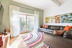 """Claire Paquin designed this walk-out basement family room to be functional for all family members: """"adult"""" space for relaxation and """"kid"""" space for play. The brown leather sectional provides comfortable seating, and the colorful art and area rug create a fun environment for all."""