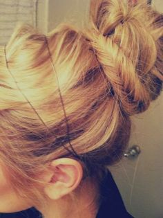 updo with a high bun and braid that is pulled over for a tousled and textured effect