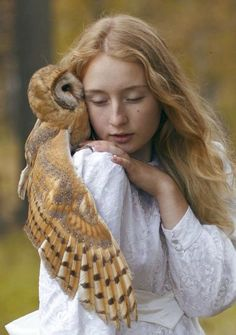 Untitled (by Katerina Plotnikova on 500px) - blonde owl on a young woman's shoulder kissing her cheek