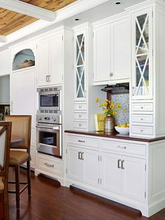 Permission to Mix X-motifs on cabinet doors near the sink and range add visual interest to these focal-point areas. Mixing door styles is one way to add interest in a white kitchen. The hutch with office supplies and a flip-down TV create a command center in this kitchen.