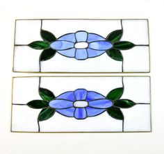 Imagine this pair of vintage, stained glass blue flowers with green leaves hanging in your window, with the sun streaming through. Theyre worked in