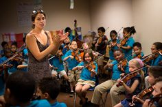 Unpacking the Science: How Playing Music Changes the Learning Brain : Kathleen Jara, co-director of the El Sistema program at the Conservatory Lab Charter School in Boston, directs orchestra students during a rehearsal for their year-end recital. (Jesse Costa/WBUR)
