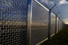 metal fence part of a metal grid fence with barbed wire at the top Diy Home Security, Safety And Security, Home Security Systems, Security Fencing, Aluminum Fence, Metal Fence, Aluminium Fencing, Vinyl Fencing, Brick Fence
