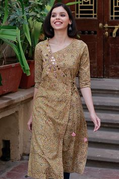 Muted hues of ochre and green in intricate Kalamkari motif block print on cotton, crafted into a calming and chic long kurta. With its stylish neckline, flattering sleeve length and tasselled doris, this design is inspired by the colours of the seaso Kalamkari Kurta, Kalamkari Dresses, Simple Kurta Designs, Kurta Designs Women, Long Kurta Designs, Printed Kurti Designs, Churidar Designs, Dress Neck Designs, Designs For Dresses