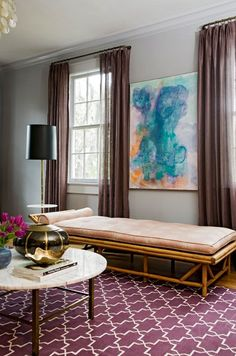 Amazing living room with Madeline Weinrib Atelier Aubergine Brooke Rug, wicker chaise lounge, brass marble top round cocktail table, plum sheers and gray walls.