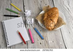 Blank notepad with colored pencils and croissant on old wooden table