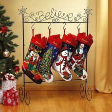 "Believe Metal Stocking Holder. Santa will come if only you believe! Perfect for homes without a fireplace mantel, this black metal holder with the word ""Believe"" in scrolled metal has 4 hooks to hold your Christmas stockings. Looks beautiful by your tree or in the living room, family room, or entryway. About 13 1/4"" x 27"" x 38 1/4"".. Price: $19.99"