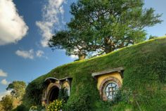 """Hobbiton, New Zealand~Hobbiton is a fictional village which appeared in the novels: """"The Lord of the Rings"""" and """"The Hobbit"""" by J.R.R. Tolkien. Hobbiton village was built as a set (for the films which were based on the Novels) is located on a farm near a little town called Matamata in northern New Zealand."""