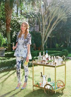Summer Style: The Garden Party. Top and pants by Lela Rose; brass and green turquoise clutch by Addison Weeks; brass oyster cuff by Emily Miranda; shark tooth and diamond ring by Cresta Bledsoe; iridescent snakeskin pumps by Charlotte Olympia; brass bar cart by Jonathan Adler. Photo by Corbin Gurkin. | Garden & Gun