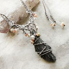 """Black Kyanite crystal amulet - this classic, strong 'feather-shaped' protection stone is always wonderful to wear. The necklace is knotted in mid-grey micro-macrame cord and highlighted with Lepidocrosite included Quartz and small clear Quartz crystals. The length is adjustable from very short down to solar plexus level.The Black Kyanite stone is approx. 6 cm (2.4"""") tall. (This stone is delicate by nature, so do be careful to protect it from accidental impacts"""