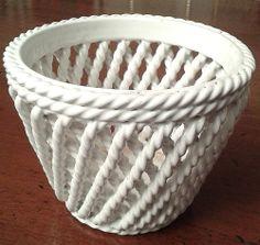 Copri vaso da fiori in ceramica bianca intrecciata.