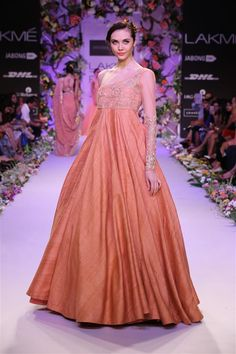 one shoulder peach gown. The dainty zari embroidery on the net yoke and sleeve adds an evening feel to the outfit.