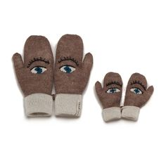 Knitted brown gloves, each with white eye outlined with black, blue iris, black lashes or brow, white cuffs, ad together they form a face, adult and child