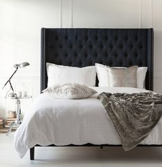 Our upholstered Versailles bed, in the rich Midnight tone, takes center stage in this soft space. Its nail head trim, as well as the metallic cushions, Rosa bedside table and Jasper lamp, add the little bit of edge this room requires.