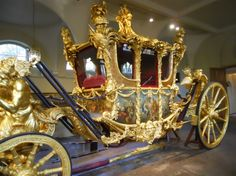 """The Gold State Coach was commissioned by King George III in 1760. He employed the well-known architect Sir William Chambers to create a """"very superb"""" coach that would be used for his Coronation and for his wedding to Princess Charlotte. The designs were so grand that the carriage was not finished in time for either important event. However, it finally made its grand appearance at the State Opening of Parliament on November 25th, 1762."""