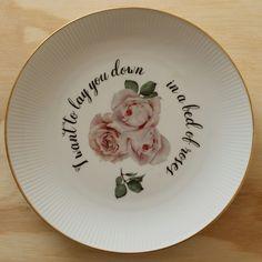 Vintage bord met een afbeelding van roos en daarbij de tekst 'i wanna lay you down in a bed of roses'. Wit plat bord met een gouden randje en wit streepjes reliëf. Doorsnede: 24 cm. Liedje: Bed of roses van Bon Jovi.