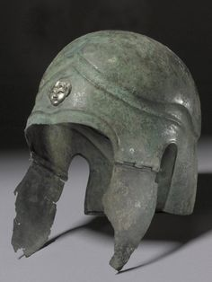 Bronze helmet of Attic type, ornamented with a silver satyr's head. The cheek-pieces may not belong to the helmet, but they are ancient and of the appropriate type. Greek 5thC BC. © The Trustees of the British Museum