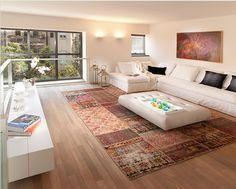 Um tapete de patchwork trouxe cor e calor para a sala com tons neutros.