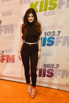 Black cropped turtle neck High waisted skinny jeans Pop of red ankle strap open toe heels Red lips Messy middle part hair Gold accessories Kylie Jenner