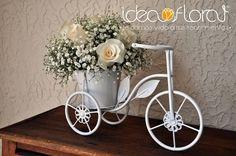 Centro de mesa en base en forma de bicicleta, hecho con rosas y baby´s breath.