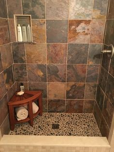 Small shower with slate and river rock tile, and a teak bench