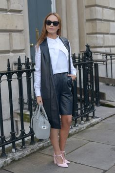 We love that this look is all clean lines and strict palette, except that pop of pink on her heels. #LFW #doubleleather #vest