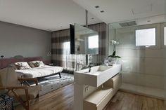 """[FINALISTA] Prêmio Casa Claudia Design de Interiores 2015 - categoria """"Apartamentos"""": Sandra Picciotto. Na suíte, um tubo suspende o espelho do banheiro e a TV do dormitório e torna-se o delimitador desses ambientes amplamente integrados, inclusive, pela continuidade do piso"""