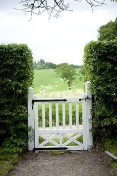 Hedge, white picket fence gate, farm